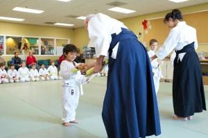 New aikido white belt student receiving his yellow belt.
